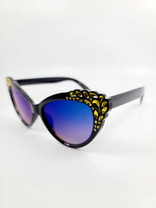 detail of black cat eye frame blue lens sunglasses with yellow gem detail