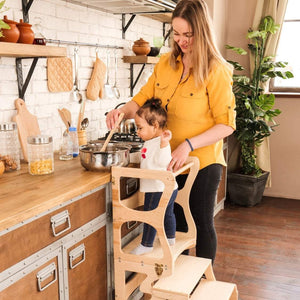 Mom with a child in the kitchen. The child stands on a high chair and reaches the countertop. Kitchen step stool chair