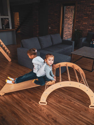 Children are playing inside.  Children's furniture Pikler Arch, Pikler ramp Color:  Naturally wood
