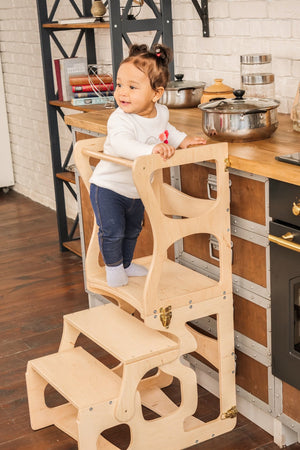 child in the kitchen. The child stands on a high chair and reaches the countertop