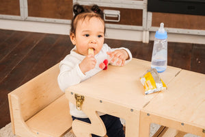 Kitchen step stool chair. The child is sitting at the table and eating. In his hands is a some food.  DIMENSIONS of  Transformer  Kitchen tower   Height: 90 cm/35 inch Width: 50 cm/19.68 inch Length: 38 cm/14,96 inch
