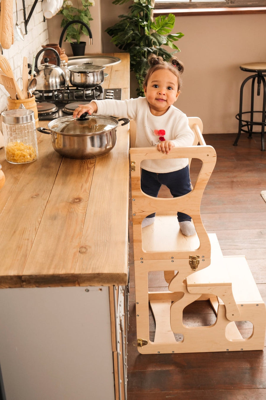 a child in the kitchen. The child stands on a high chair and reaches the countertop