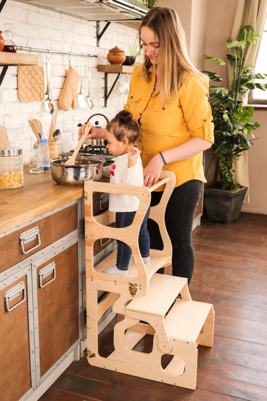 Mom with a child in the kitchen. The child stands on a high chair and reaches the countertop. Kitchen step stool chair.