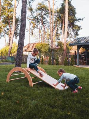 Two children are playing outside. Children's furniture Pikler Arch, Pikler ramp . Color:  Naturally wood