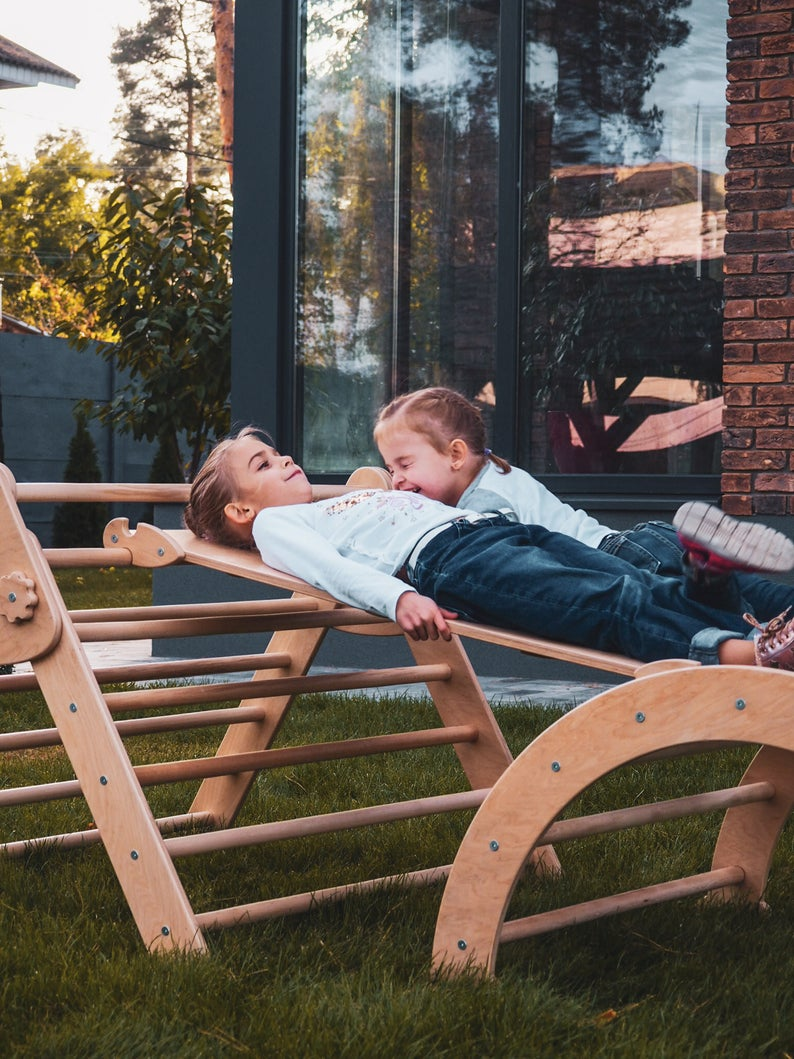 Two children are playing outside. Children's furniture Pikler Arch, Pikler ramp and Pikler Triangle Color:  Naturally wood