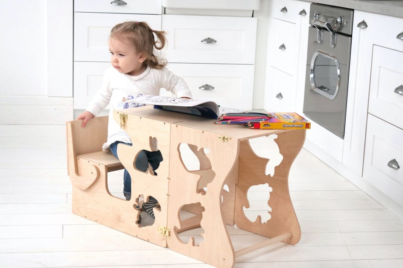 Kitchen step stool chair with animals. The child is sitting at the table. In his hands is a pencil on the table and coloring.  DIMENSIONS of  Transformer  Kitchen tower   Height: 90 cm/35 inch Width: 50 cm/19.68 inch Length: 38 cm/14,96 inch