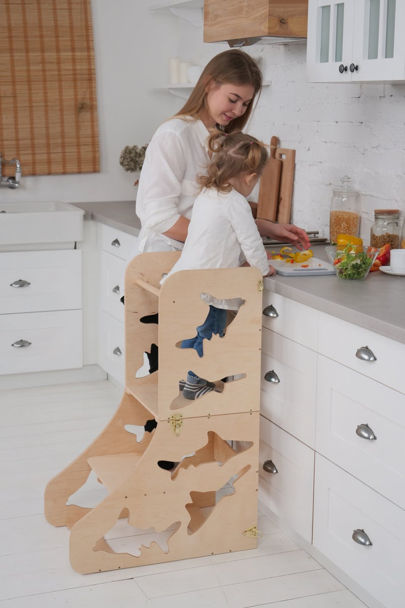Learning stool The learning towe Mom with a child in the kitchen. The child stands on a high chair and reaches the countertop. Kitchen step stool chair with animals.  DIMENSIONS of  Transformer  Kitchen tower   Height: 90 cm/35 inch Width: 50 cm/19.68 inch Length: 38 cm/14,96 inch