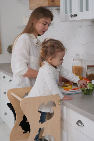 Mom with a child in the kitchen. The child stands on a high chair and reaches the countertop. Kitchen step stool chair with animals.  DIMENSIONS of  Transformer  Kitchen tower   Height: 90 cm/35 inch Width: 50 cm/19.68 inch Length: 38 cm/14,96 inch