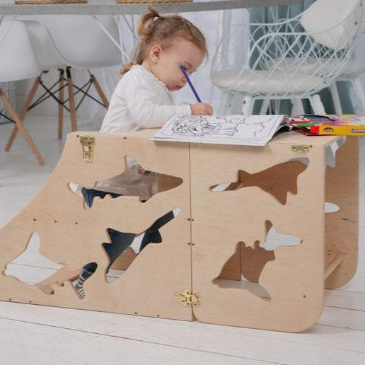 Learning stool The learning tower. Kitchen step stool chair with animals. The child is sitting at the table. In his hands is a pencil on the table and coloring.  DIMENSIONS of  Transformer  Kitchen tower   Height: 90 cm/35 inch Width: 50 cm/19.68 inch Length: 38 cm/14,96 inch