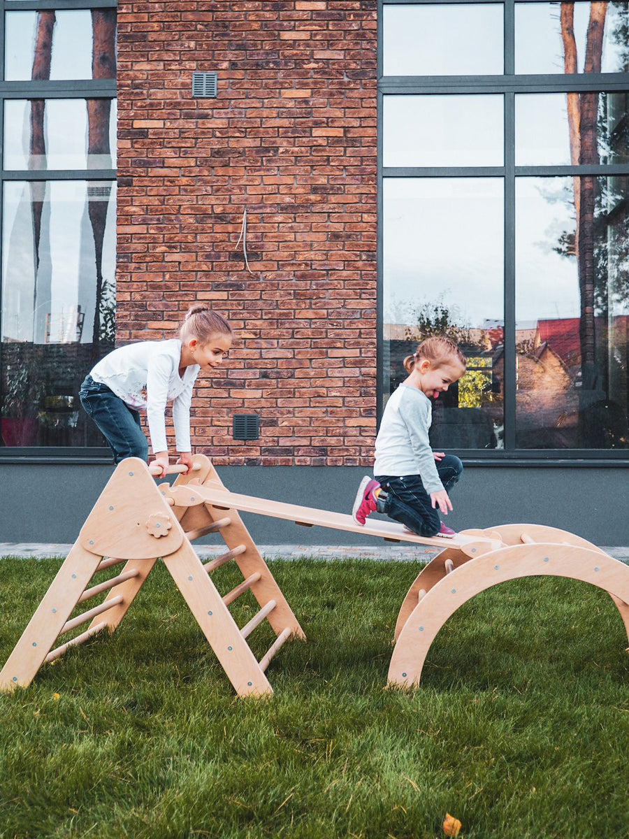 Two children are playing outside. Children's furniture Pikler Arch, Pikler ramp and Pikler Triangle. Color:  Naturally wood