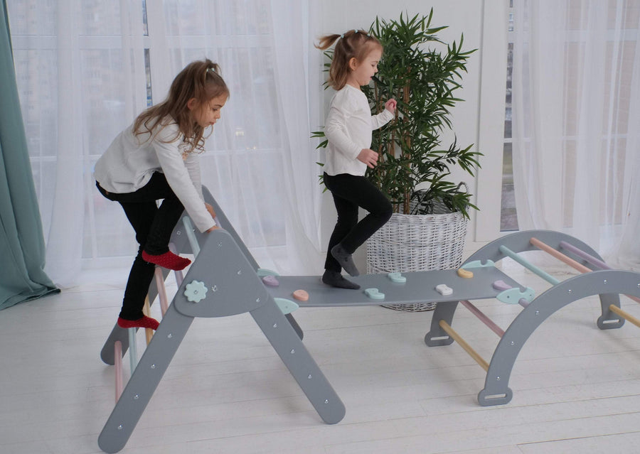 Children are playing inside. Children's furniture Pikler Arch, Pikler ramp and Pikler Triangle. Color: Grey+Varicoloured