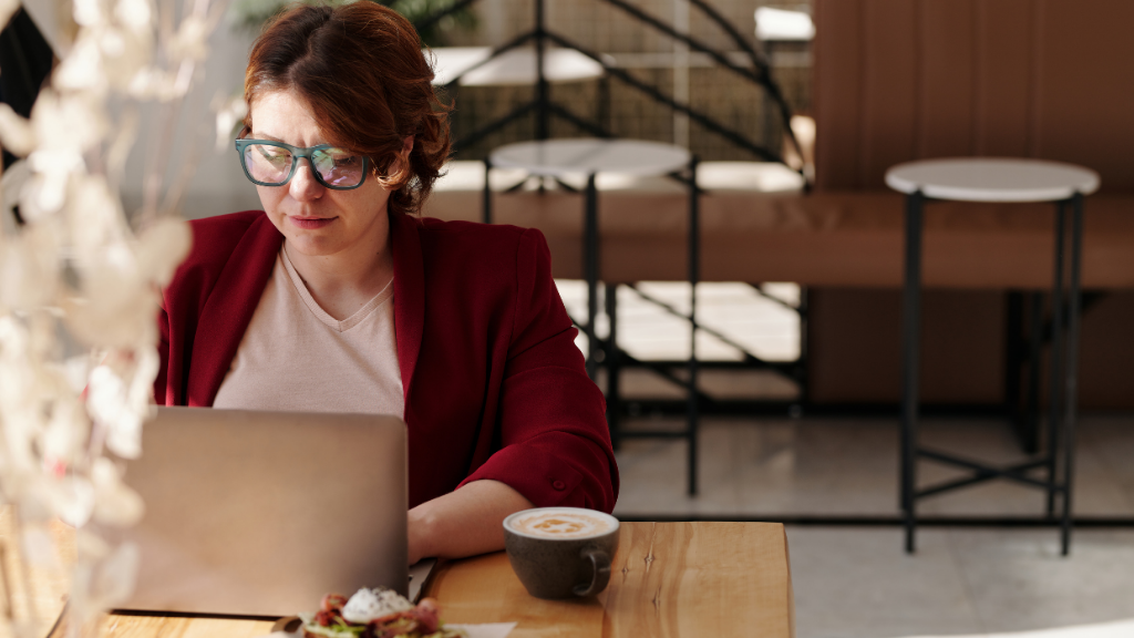 Woman in a red blazer working on a laptop