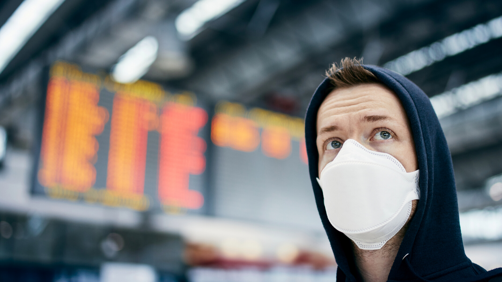 Man wearing a mask in healthrow airport terminal