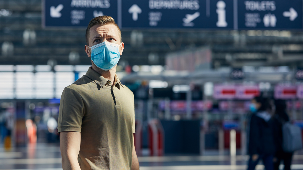 Man wearing a surgical mask in an airport