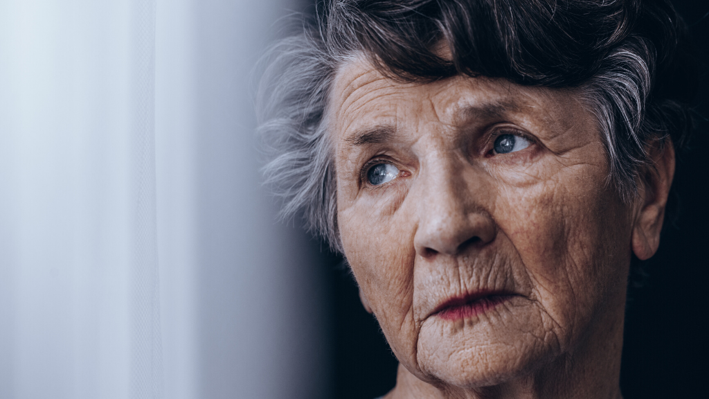 Old woman standing beside the window