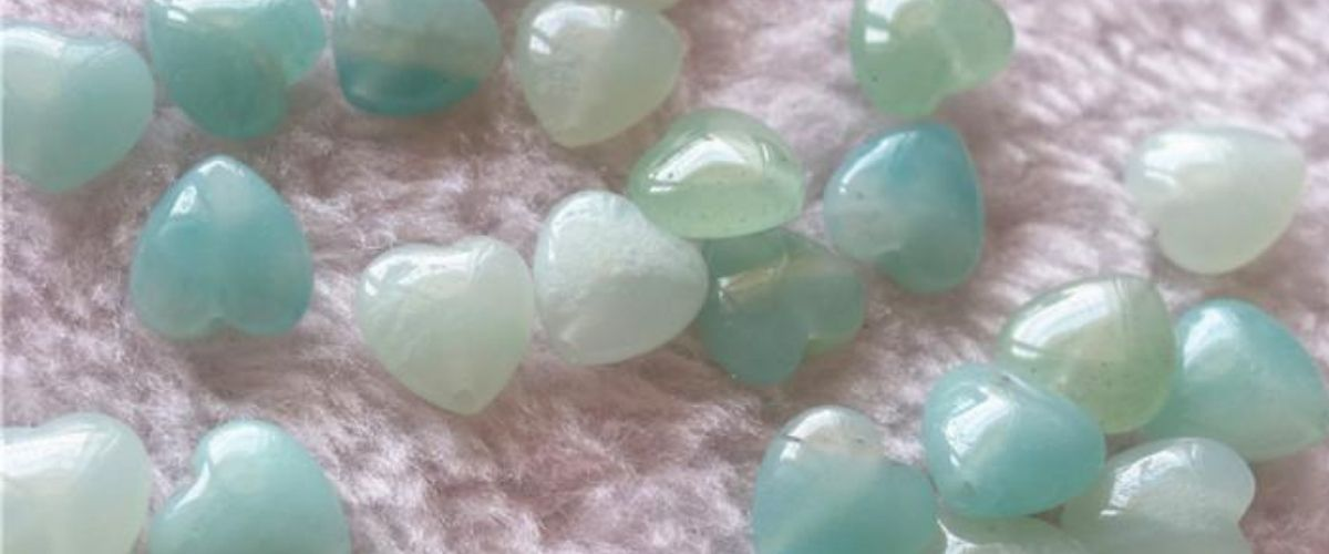 Amazonite heart shaped gemstones on a pink fluffy rug