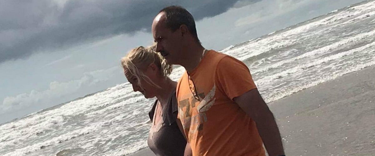 Photo of Andy with his Wife Nicky strolling on beach paddling on sea