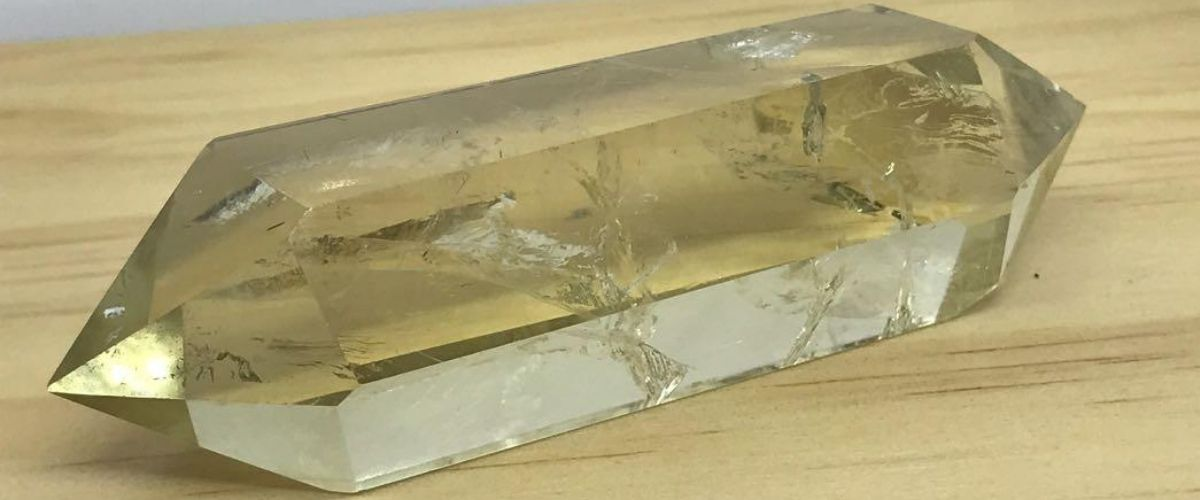 Large piece of Natural Citrine point on a wooden table
