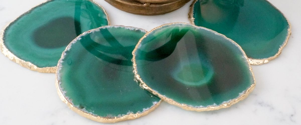 Four Green Agate coasters with gold leaf rims on a white table