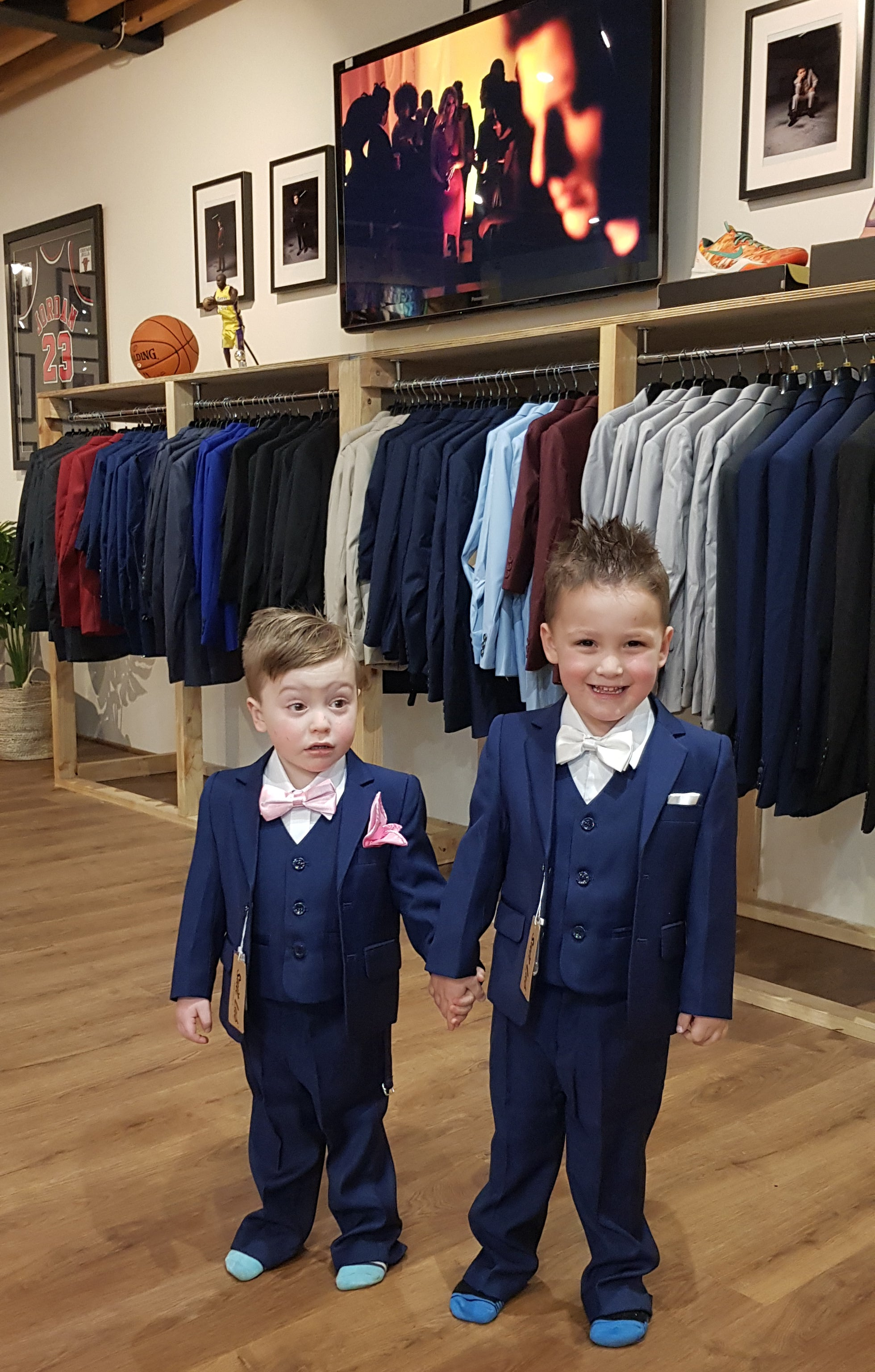 two brothers one with navy suits, one with pink bow tie and pocket square and the other one with white accessories