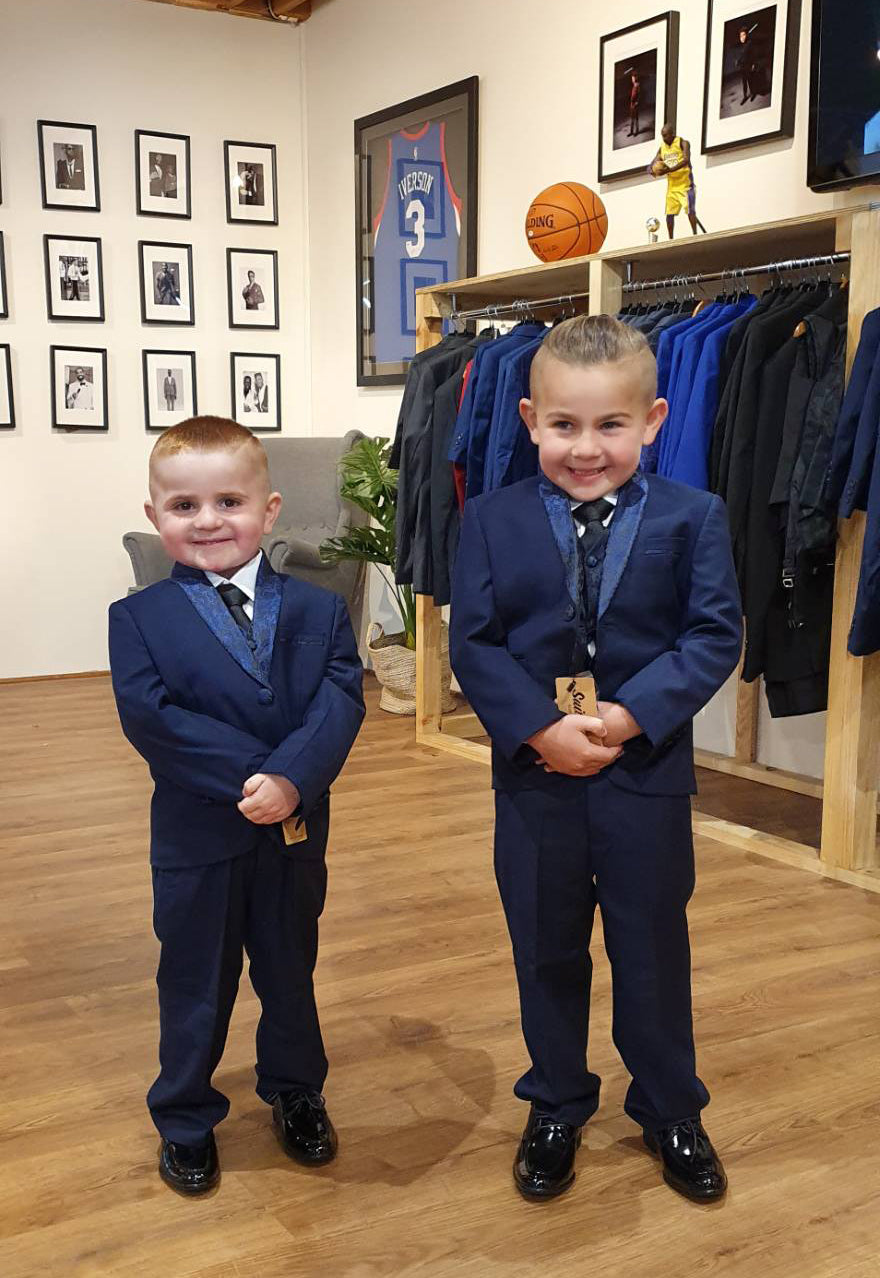 two brothers wearing matching dark navy suit