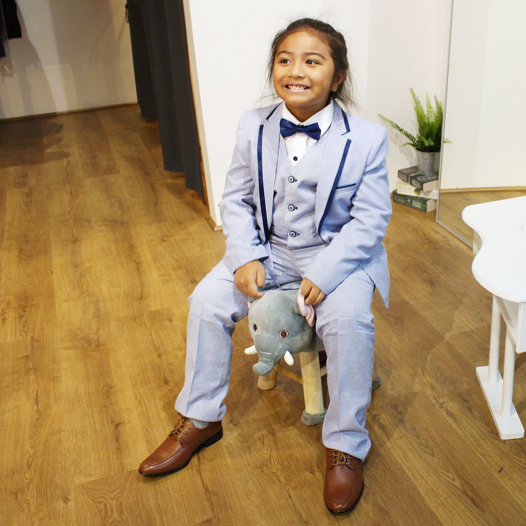 boy with checkered light blue suit, white shirt and navy bow tie, and a brown shoes