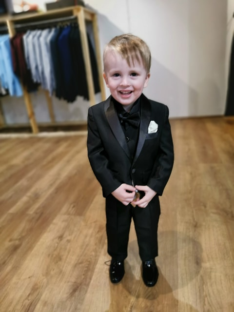 bow with black tuxedo, black shirt, black bow tie and black shiny shoes. complimented with white pocket square for a nice contrast