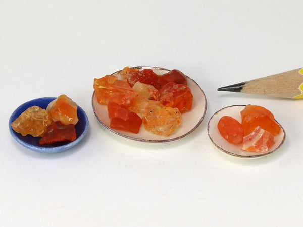 Tiny orange, red & yellow fire opal crystals in 1:12 scale china bowls.  Side view.