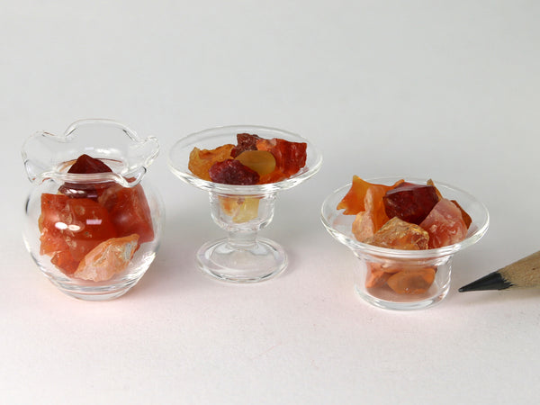 Tiny orange, red & yellow fire opal crystals in assorted 1:12 scale glass dishes.  Side view.