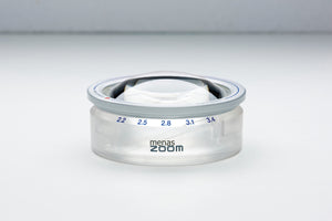 Circular magnifier with twist-to-extend feature retracted and 'menas zoom' on base of product.