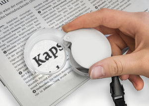 Circular magnifier with white fold-out case and LED being used to magnify a newspaper