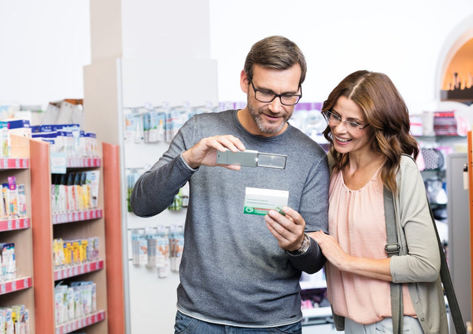 Man and woman using slide out magnifier (Easy Pocket XL) to read small print on medicine packet.