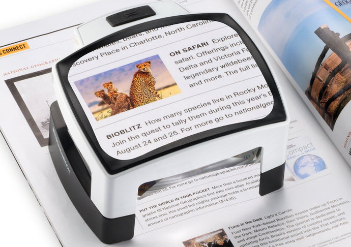 Large, rectangular reading magnifier with sleek design, white and black outlines. Black button for LED light and open base under magnifier