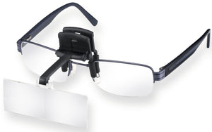 Magnifying lens on black carrier, clipped onto glasses.