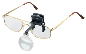 Monocular (circular) lens on black arm and clip, attached to glasses.