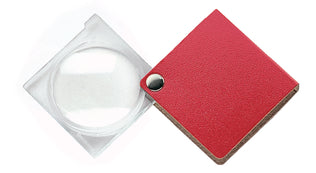 Circular magnifier with clear square housing, attached to red square case.