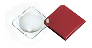 Circular magnifier inside clear square setting, with attached fold-out red case