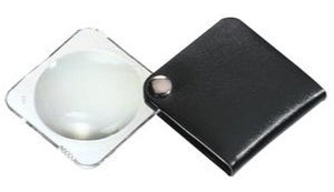 Circular magnifier inside clear square setting, with attached fold-out black case