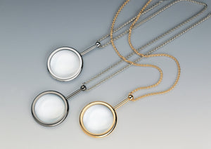 Small pendant style, circular magnifiers in gold and chrome with matching neck chains.