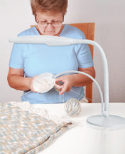 Load image into Gallery viewer, Woman sitting down, knitting underneath circular magnifier and lamp.
