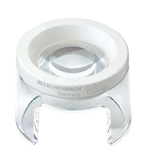 Small circular magnifier raised above work surface by clear stand, has an opening in base for working under magnifier