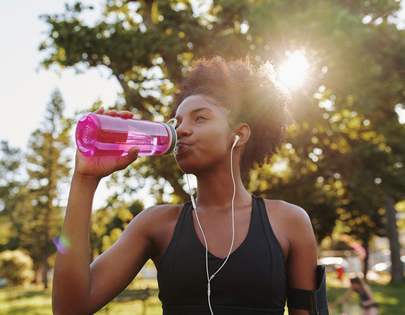 woman in workout clothes drinking water