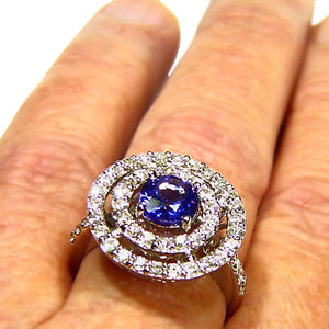 Stunning all natural Tanzanite surrounded by a wall of diamonds in this 14k white gold ring