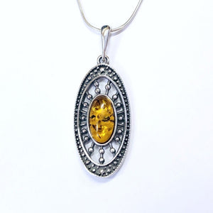 "Oval dotted design pendant with honey amber center and 18""snake sterling silver chain."