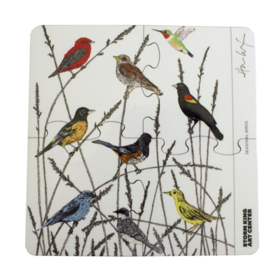 Rounded-square trivet of four connected glass coasters of seasonal birds in native grass.