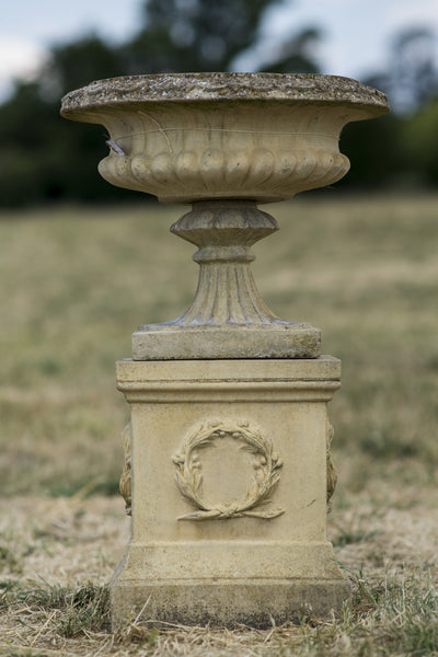 Pair of English Composite Stone Urns on Plinths