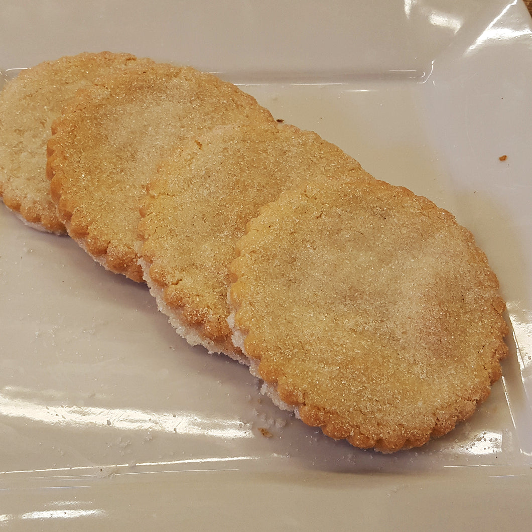 Four large sugar cookies on a white plate