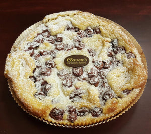 Cherry frangipane tart topped with cherries, powdered sugar and the Clasen chocolate disk