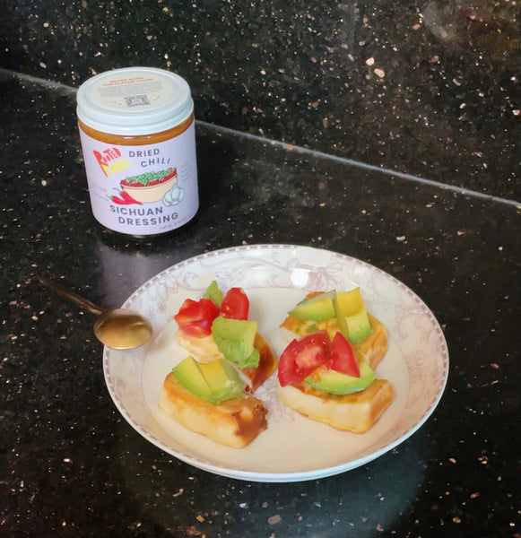 Four bite-sized steam buns topped with avocado and tomato with a jar of Dried Chili Sichuan Dressing next to it.