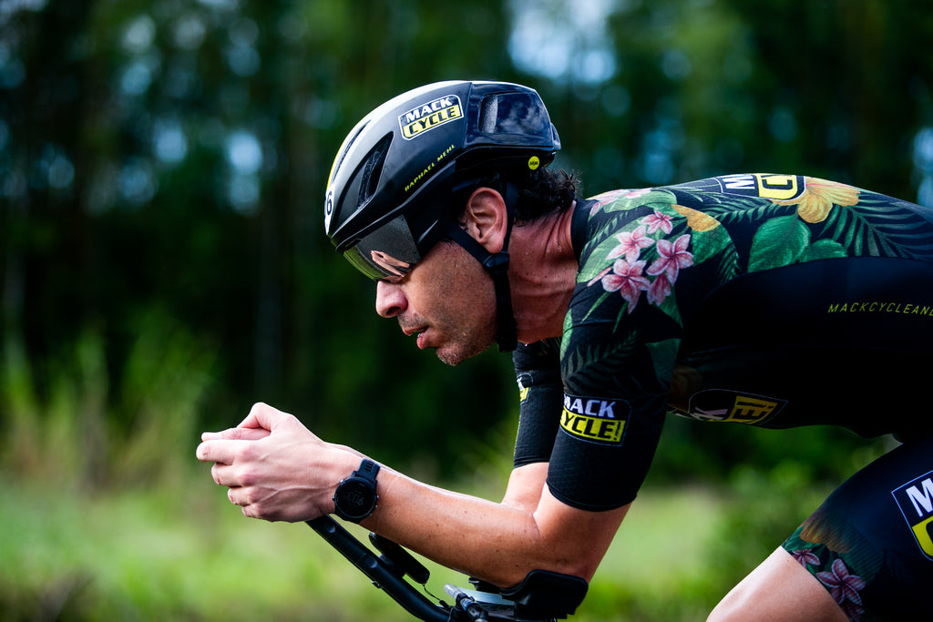 upclose shot of triathlete racing wearing a Giro Vanquish helmet against a green nature background. Triathlete, Raphael Mehl, is racing wearing a black floral hibiscus Mack Cycle Tri Suit.